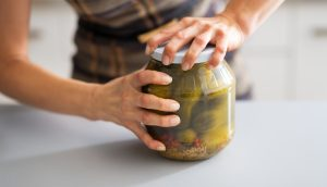 Frau versucht, ein Einmachglas mit Gurken zu öffnen