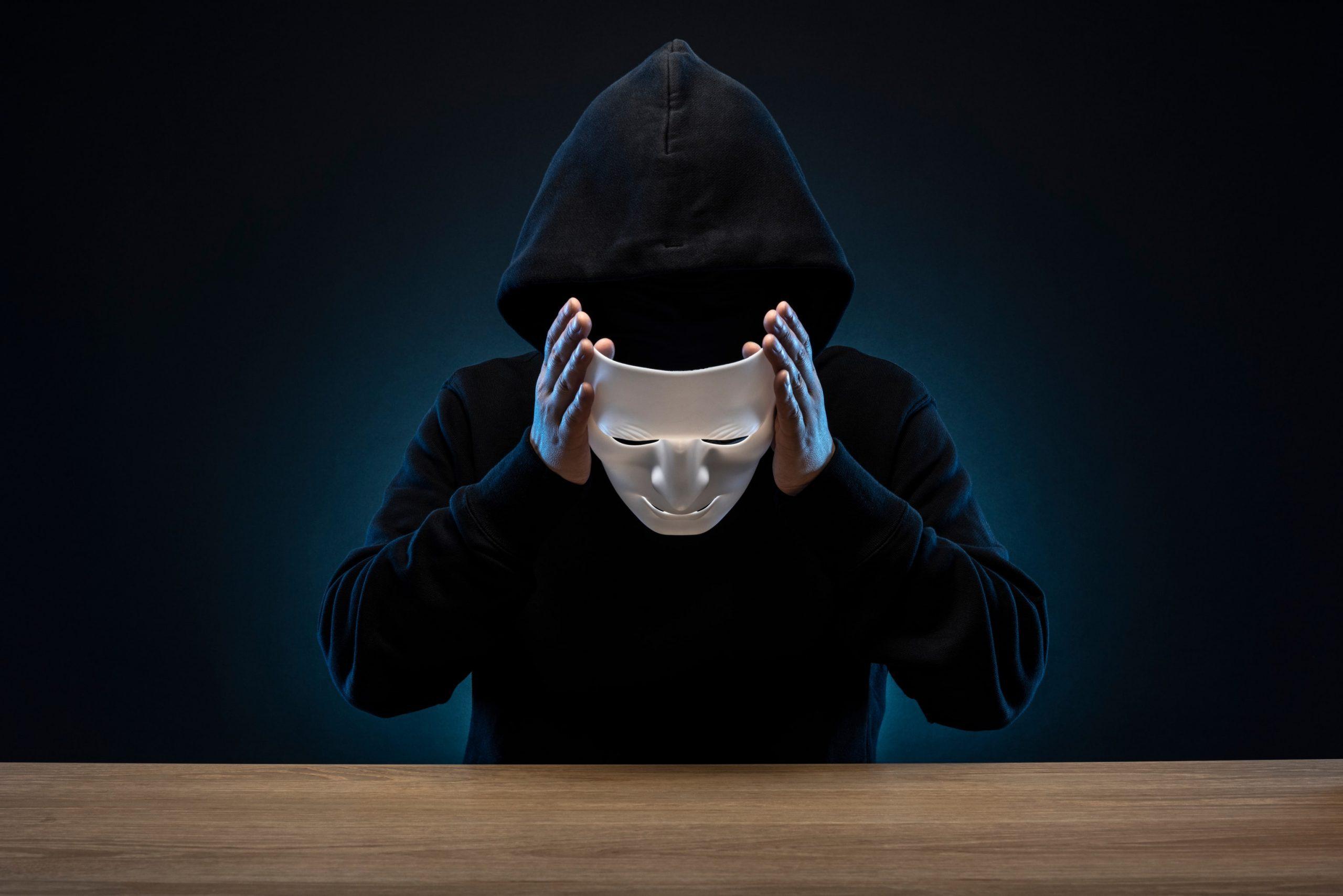 Mann mit Hoodie nimmt sich vor dunklem Hintergrund seine Maske ab