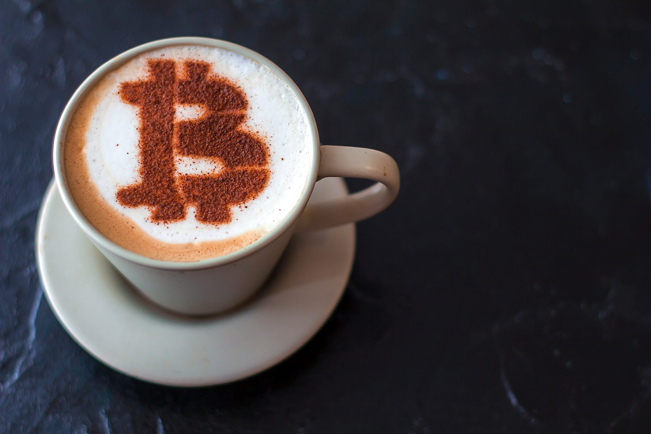 coffee cappuccino in a white cup with a symbol Bitcoin of cinnamon on milk foam