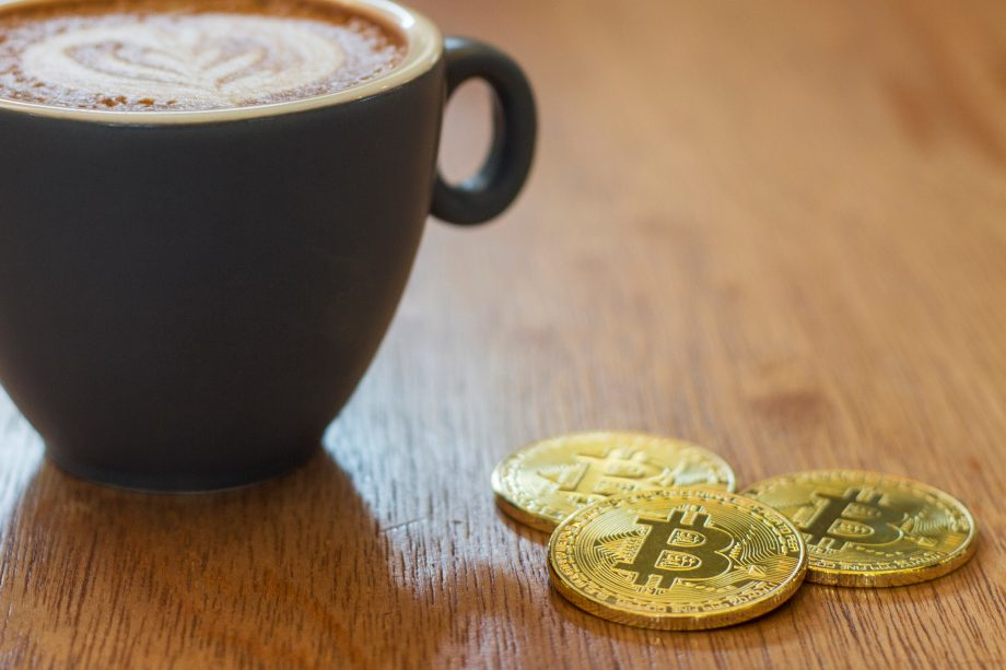 concept of business trading latte coffee with pieces of golden bitcoin Cryptocurrency in a cafe