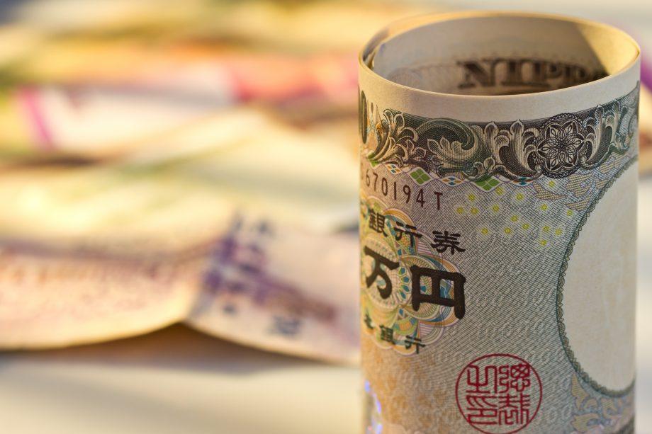 Eine zusammengerollte Yen-Note, im Hintergund weitere Geldscheine
