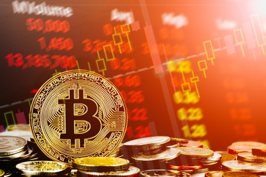 Bitcoin-Münze vor rotem Trading-Konzepthintergrund