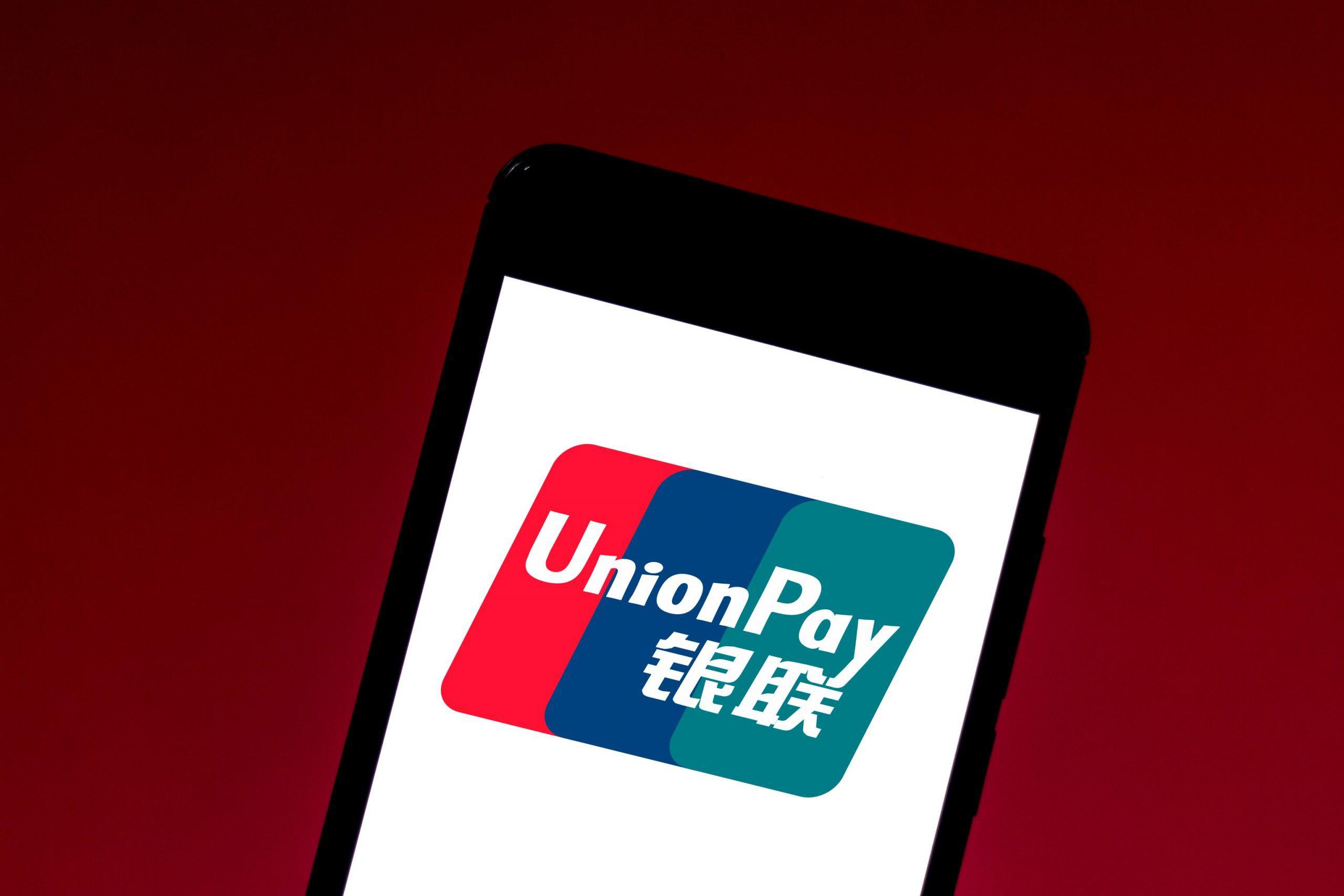 Smartphone mit UnionPay-Logo vor rotem Hintergrund