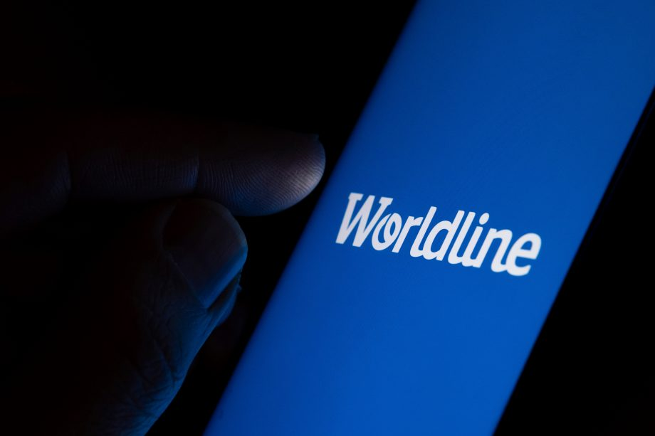 tone / United Kingdom - February 4 2020: Worldline payment company logo on the blue screen and finger about to touch it. Concept photo.