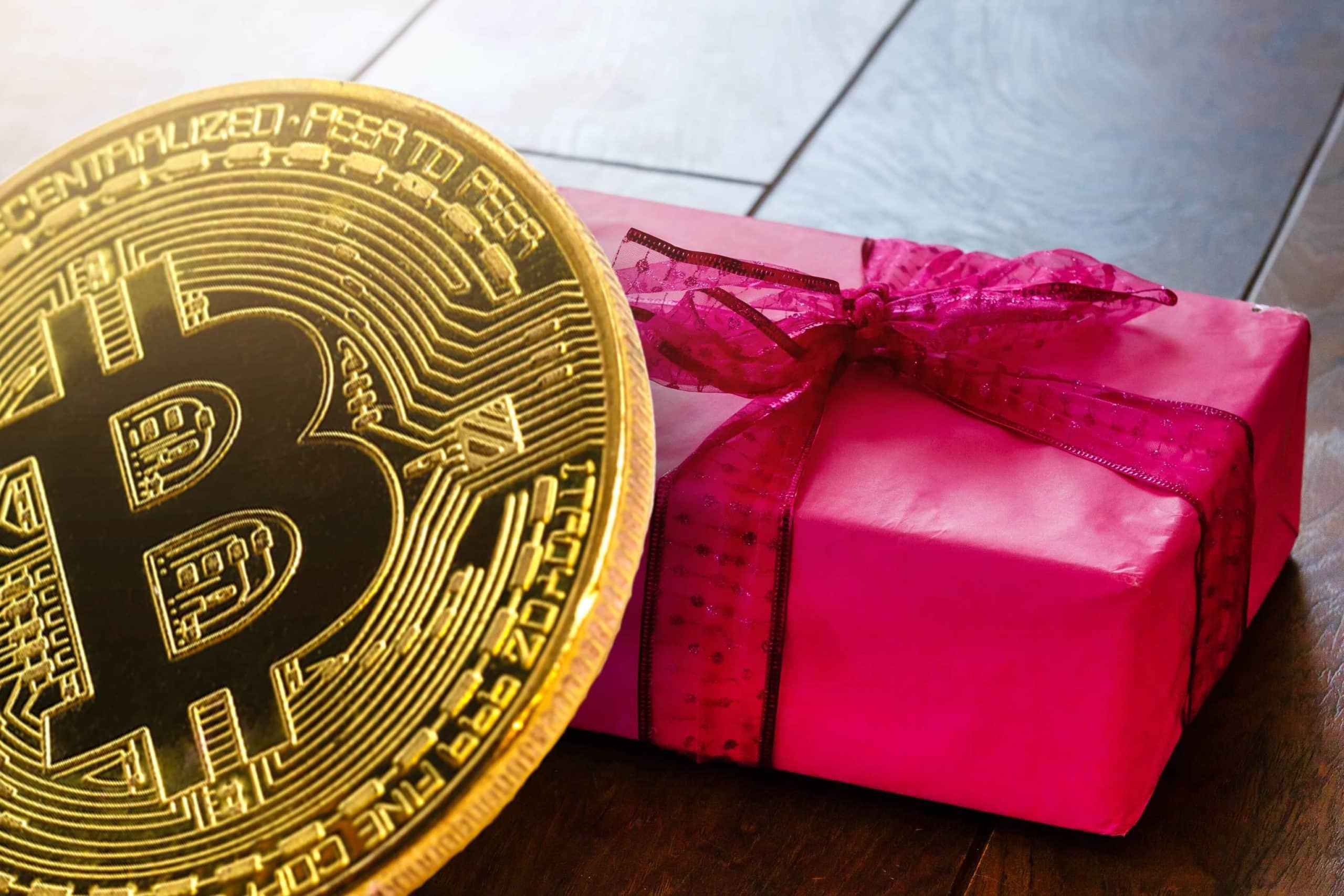 Bitcoin Münze vor einem roten Geschenk