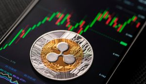 Ripple-Münze vor Smartphone Display, das einen Kurs-Chart zeigt