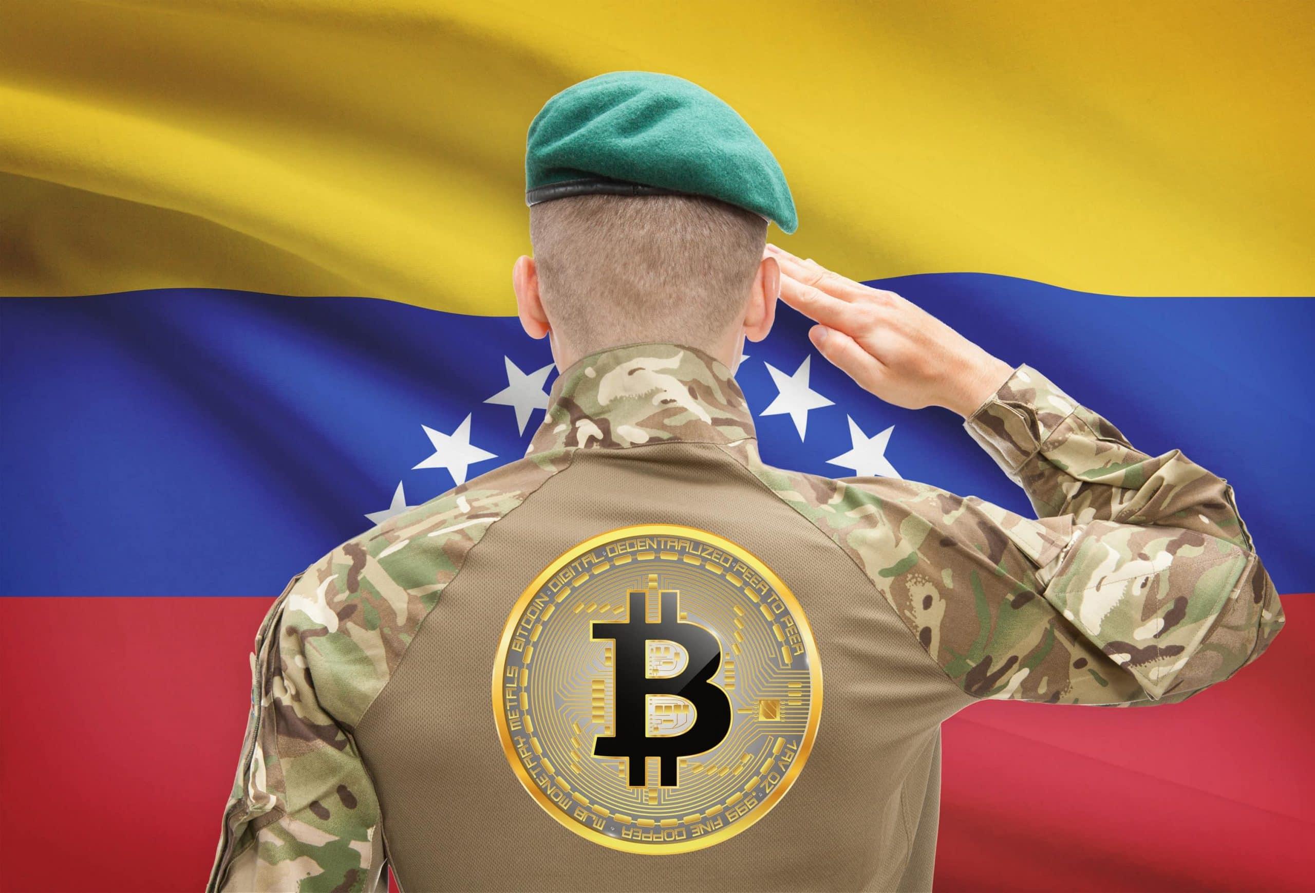 Salutierender Soldat vor Venezuala-Flagge, auf dem Rücken trägt er das Bitcoin-Logo