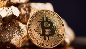 Bitcoin-Münze steht vor einem Haufen Gold