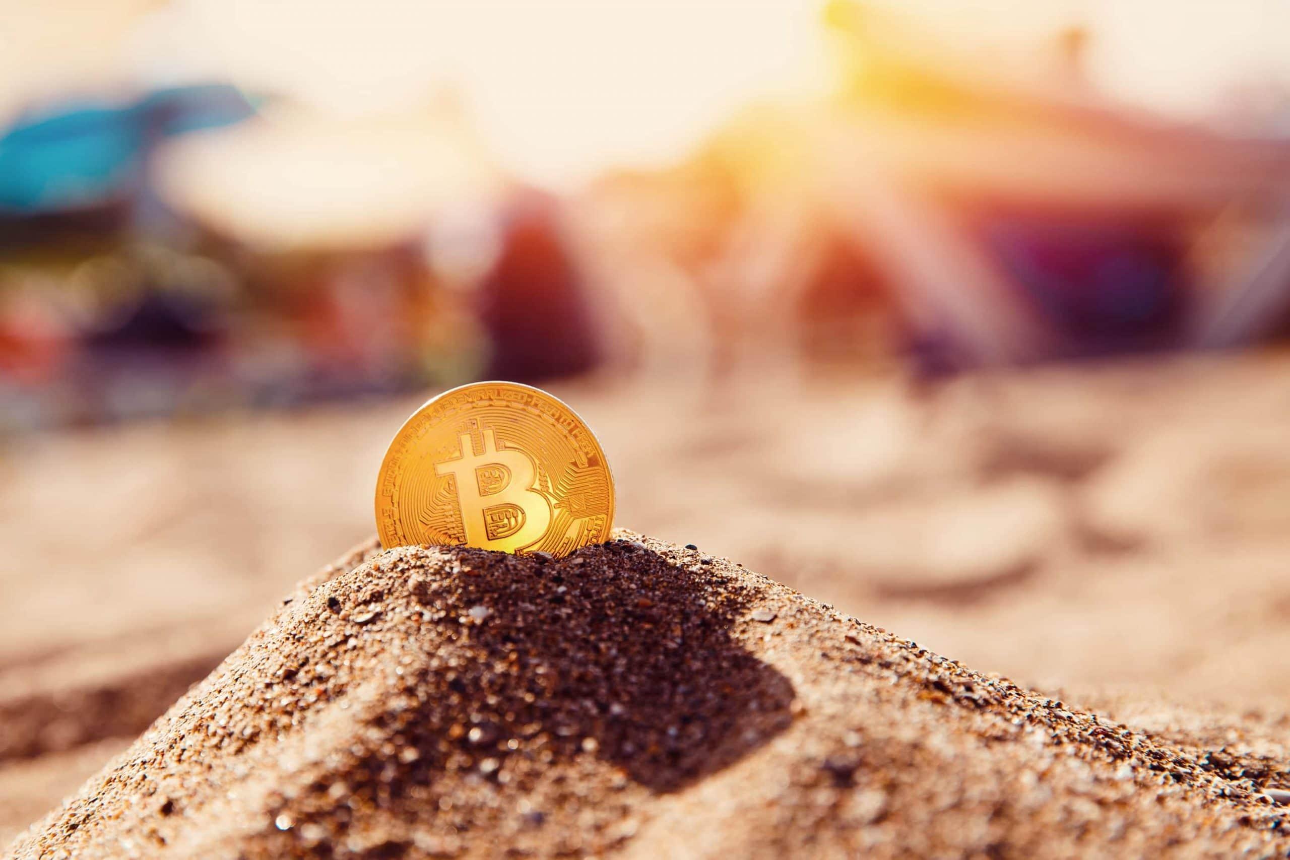 Bitcoin-Münze steckt im Sandhaufen