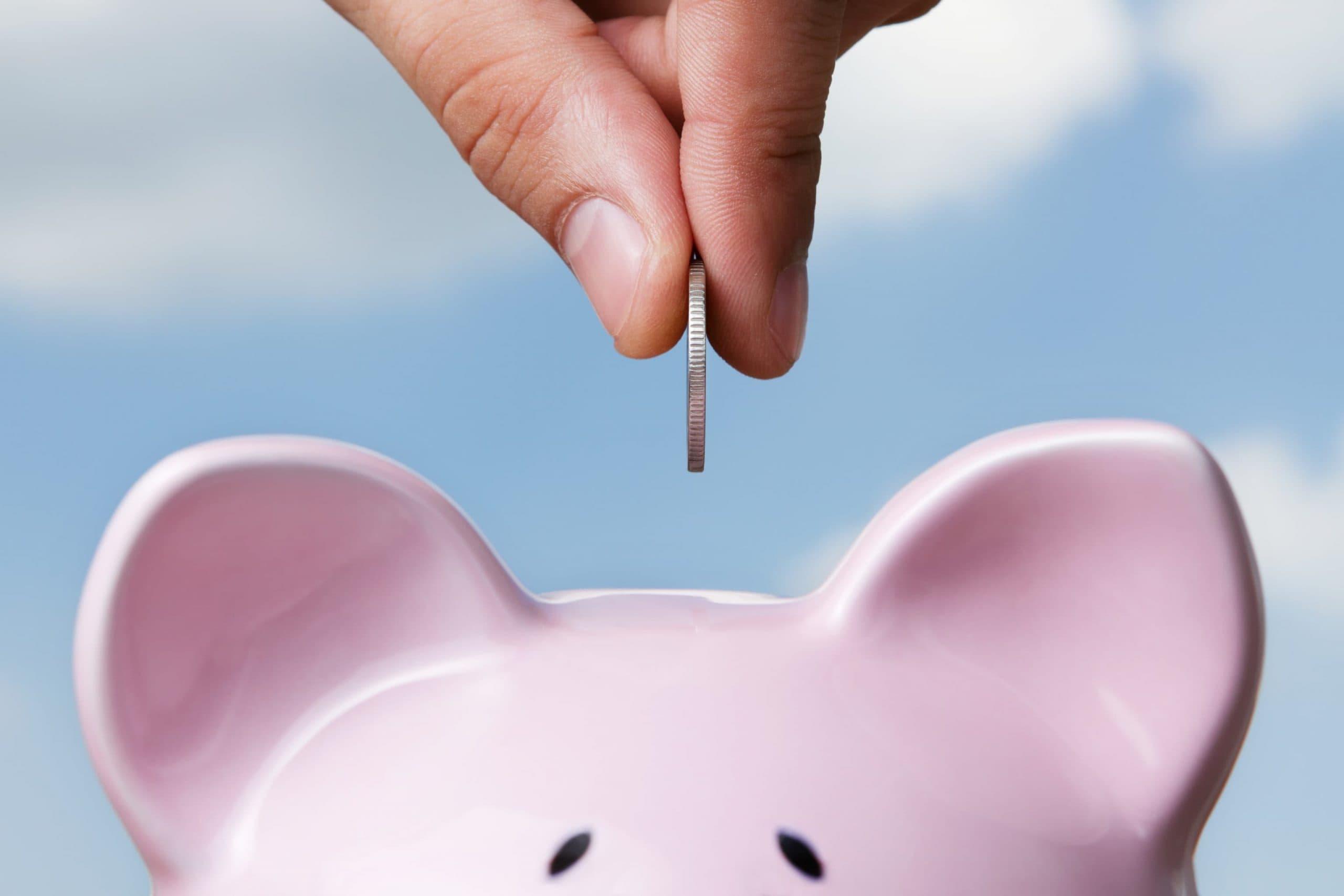 Hand steckt Münze in Sparschwein