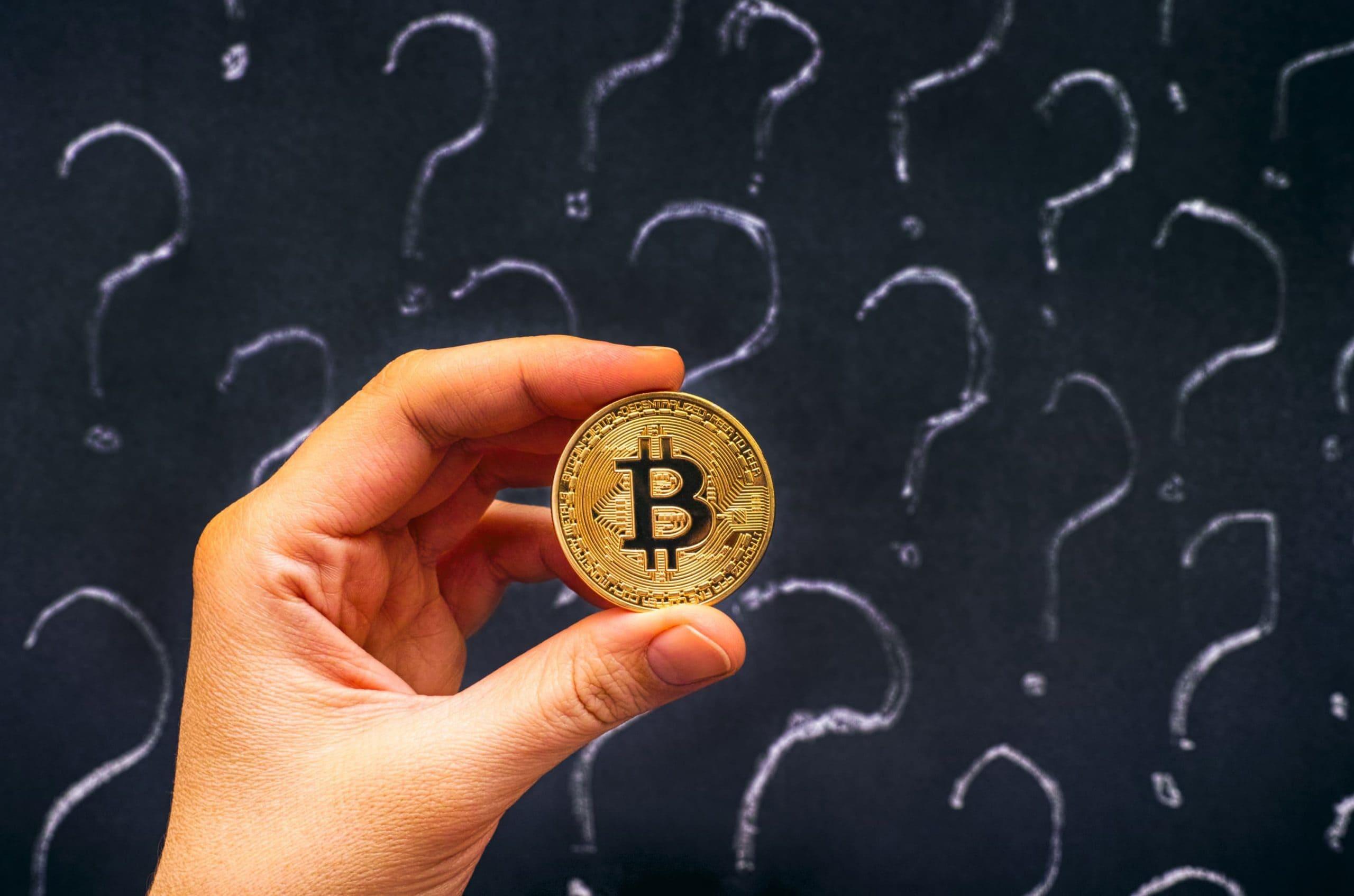 Ein Hand hält eine Bitcoin-Münze, im Hintergrund eine Tafel voller Fragezeichen