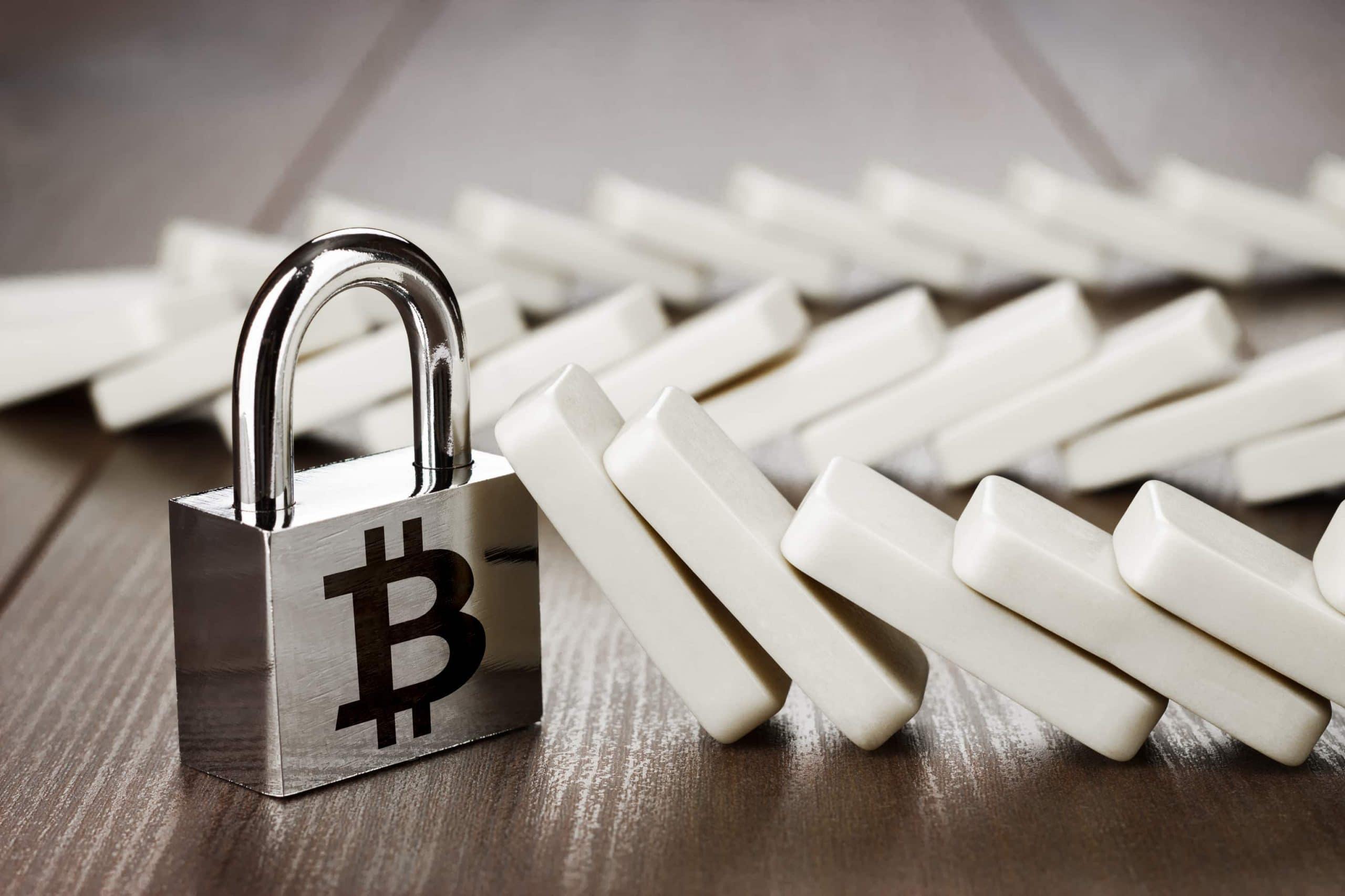 Ein Vorhängeschloss mit Bitcoin-Logo hält den Sturz einer Domino-Reihe auf