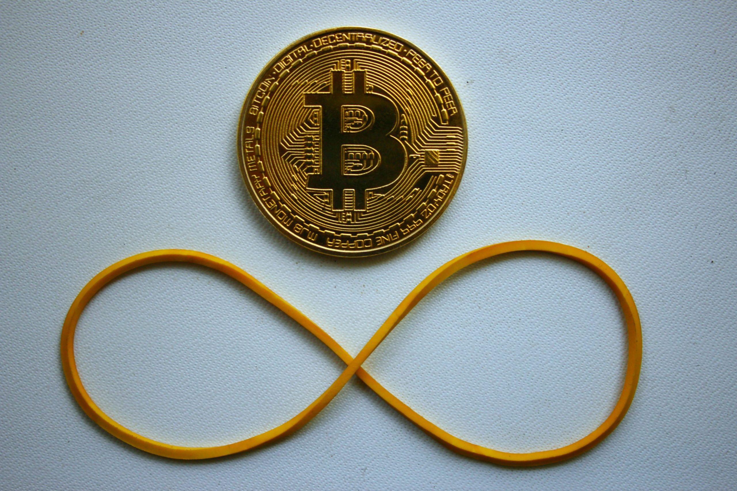 Bitcoin-Münze, darunter ein Gummiband, das in Form des Undendlichkeitzeichens gelegt ist