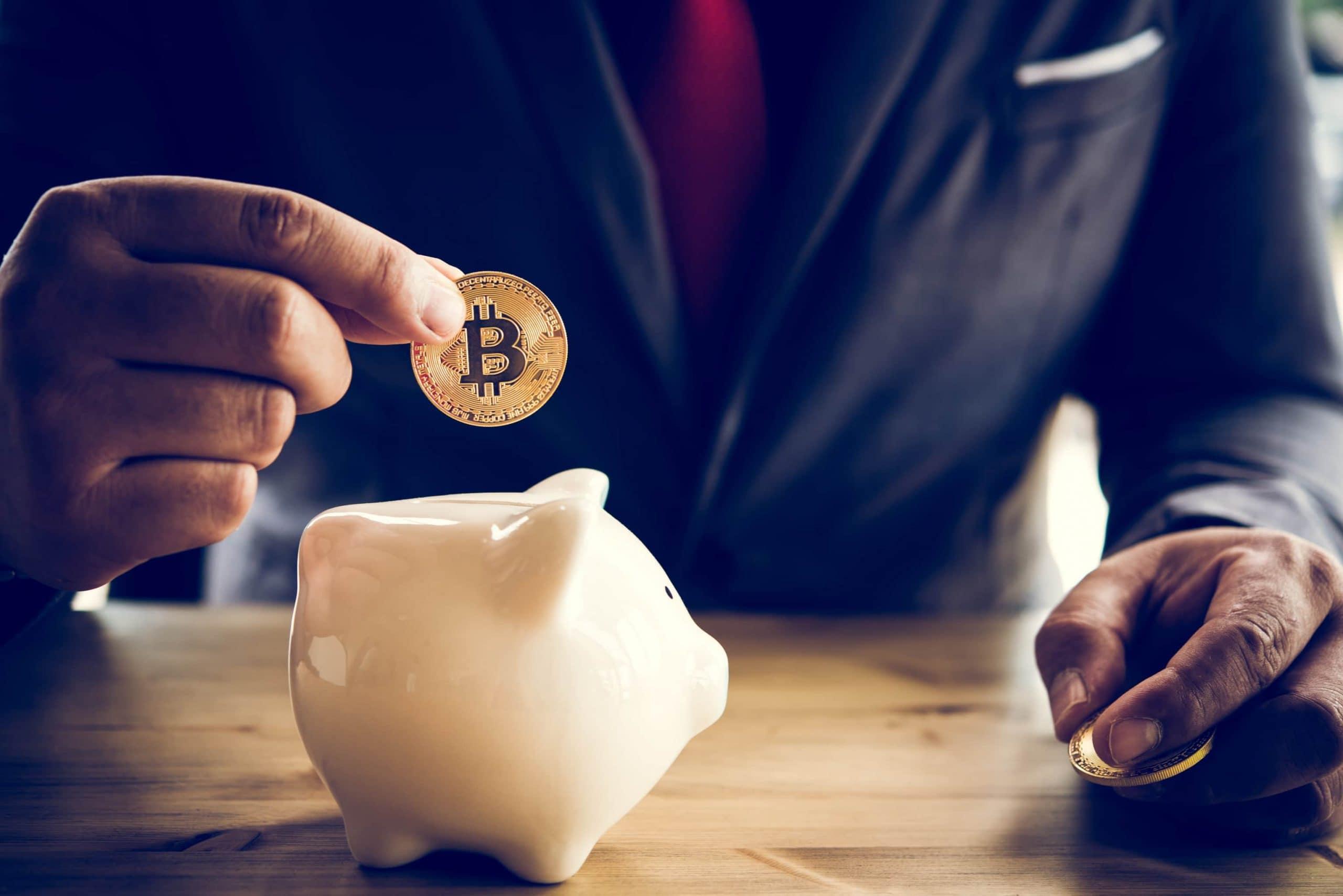 Ein Geschäftsmann steckt eine Bitcoin-Münze in ein Sparschwein