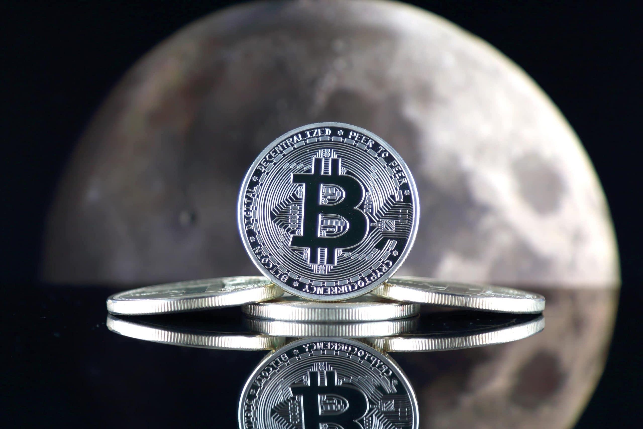 Bitcoin-Münzen, im Hintergrund der Mond