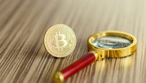 Eine Bitcoin-Münze steht neben einer Lupe auf einem Holztisch
