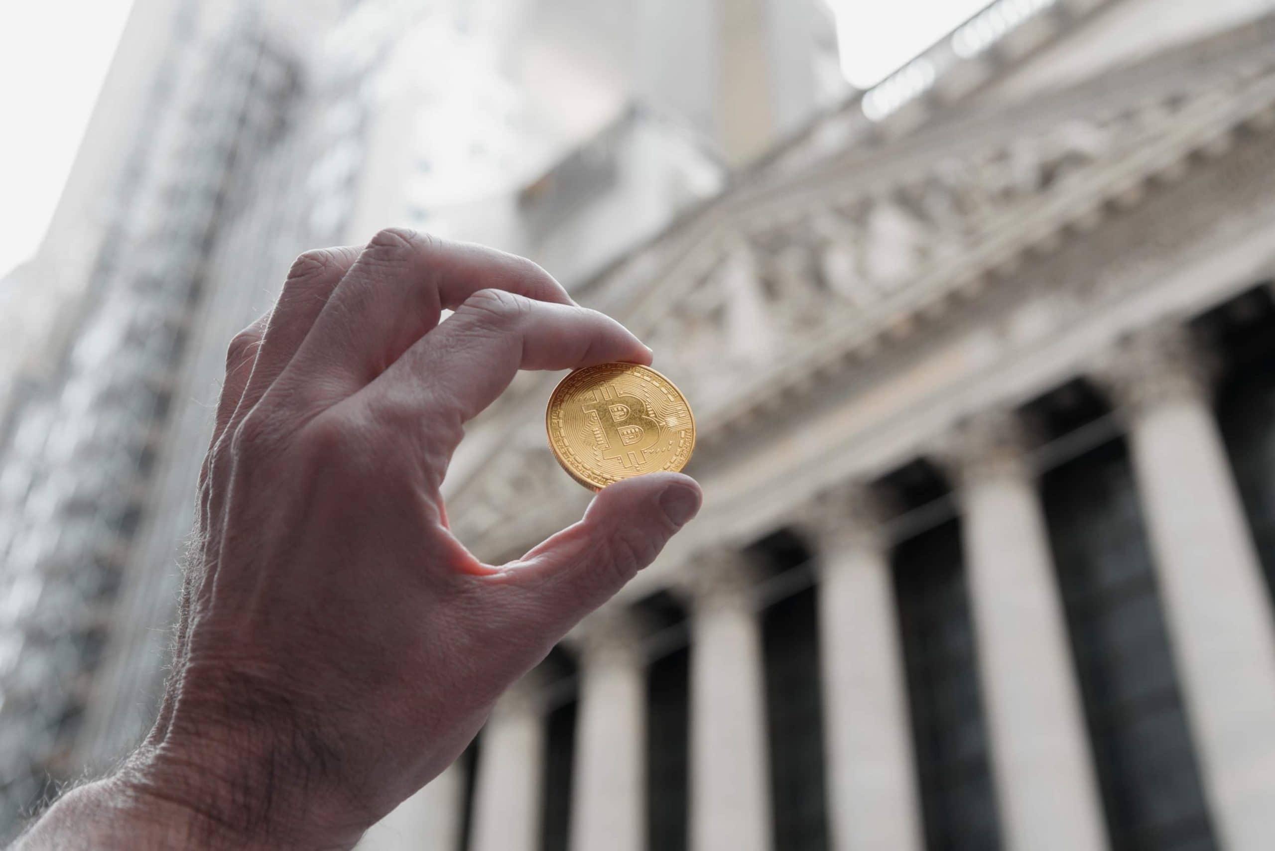 Ein Mann hält eine Bitcoin-Münze, im Hintergrund der New Yorker Börse in der Wall Street