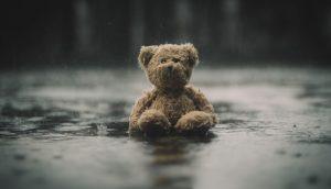 Ein Teddybär sitzt im Regen