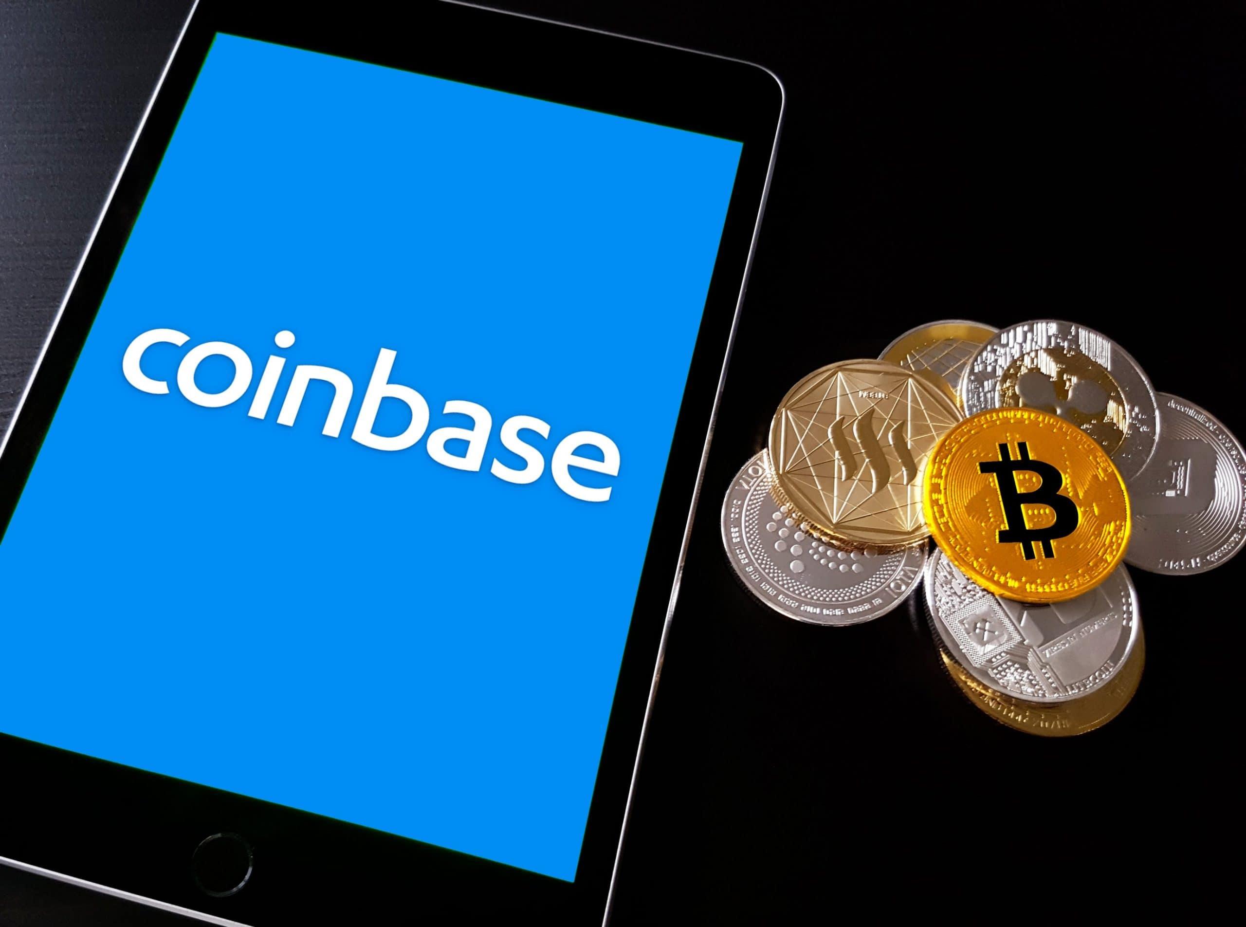 Coinbase Logo auf Smartphone Display, daneben ein Haufen mit diversen Krypto-Münzen