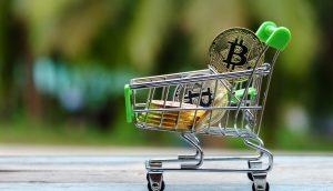 Mit Bitcoin-Münzen gefüllter Spielzeug-Einkaufswagen