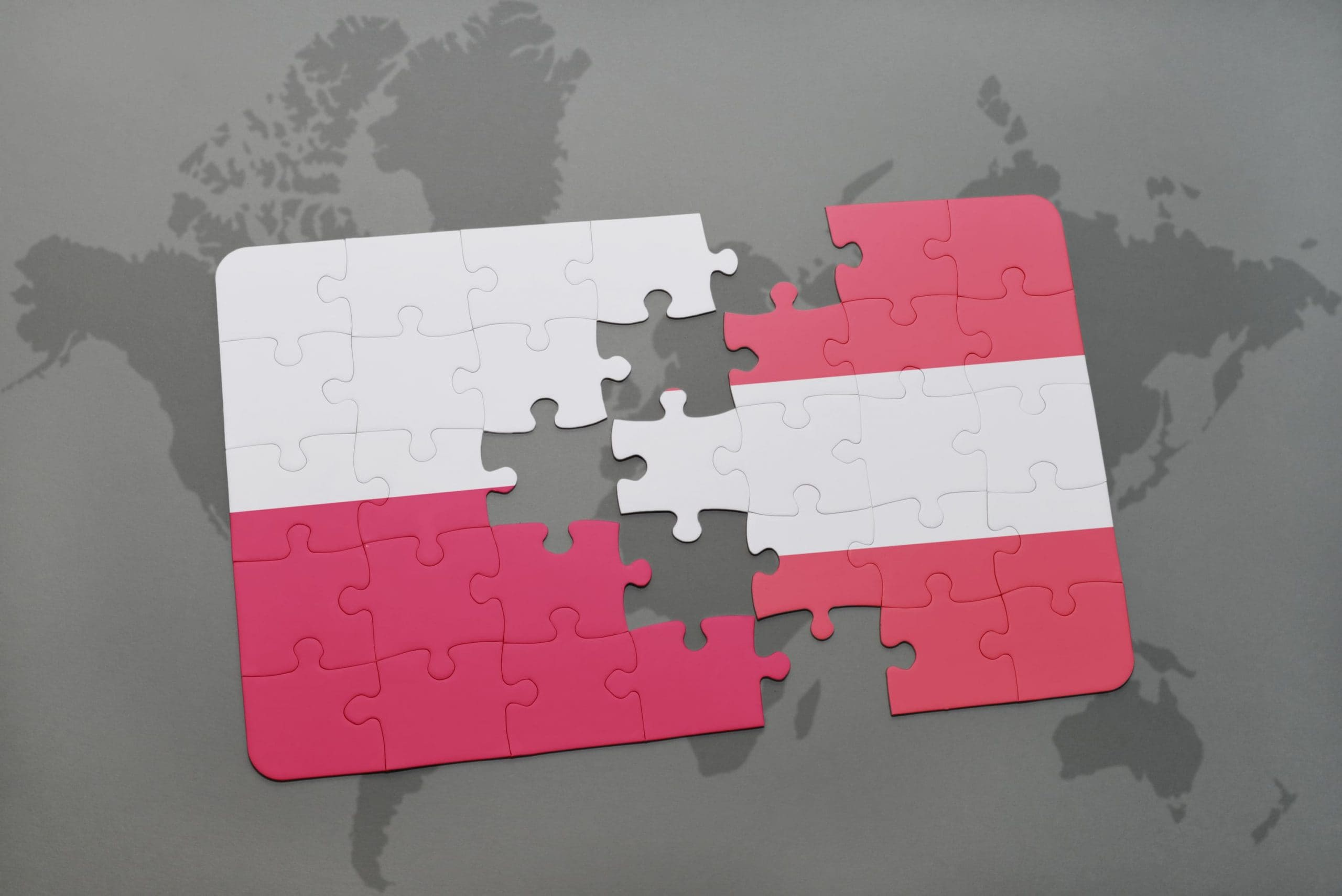 Zusammenpassende Puzzle-Teile in den Farben Östereichs und Polen,