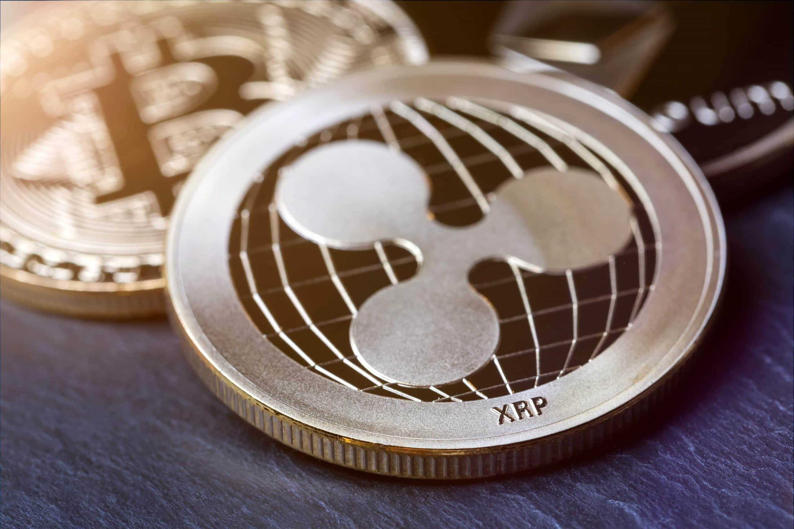 Ripple und Bitcoin auf einem dunkeln Holzuntergrund.