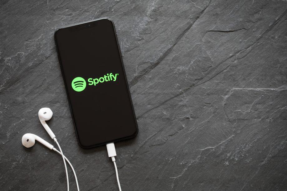 Das Spotify-Logo auf dem Bildschirm eines schwarzen Smartphones, das auf einem graufarbendem Keramikuntergrund liegt. Weiße Kopfhörer sind an das Telefon angeschlossen.