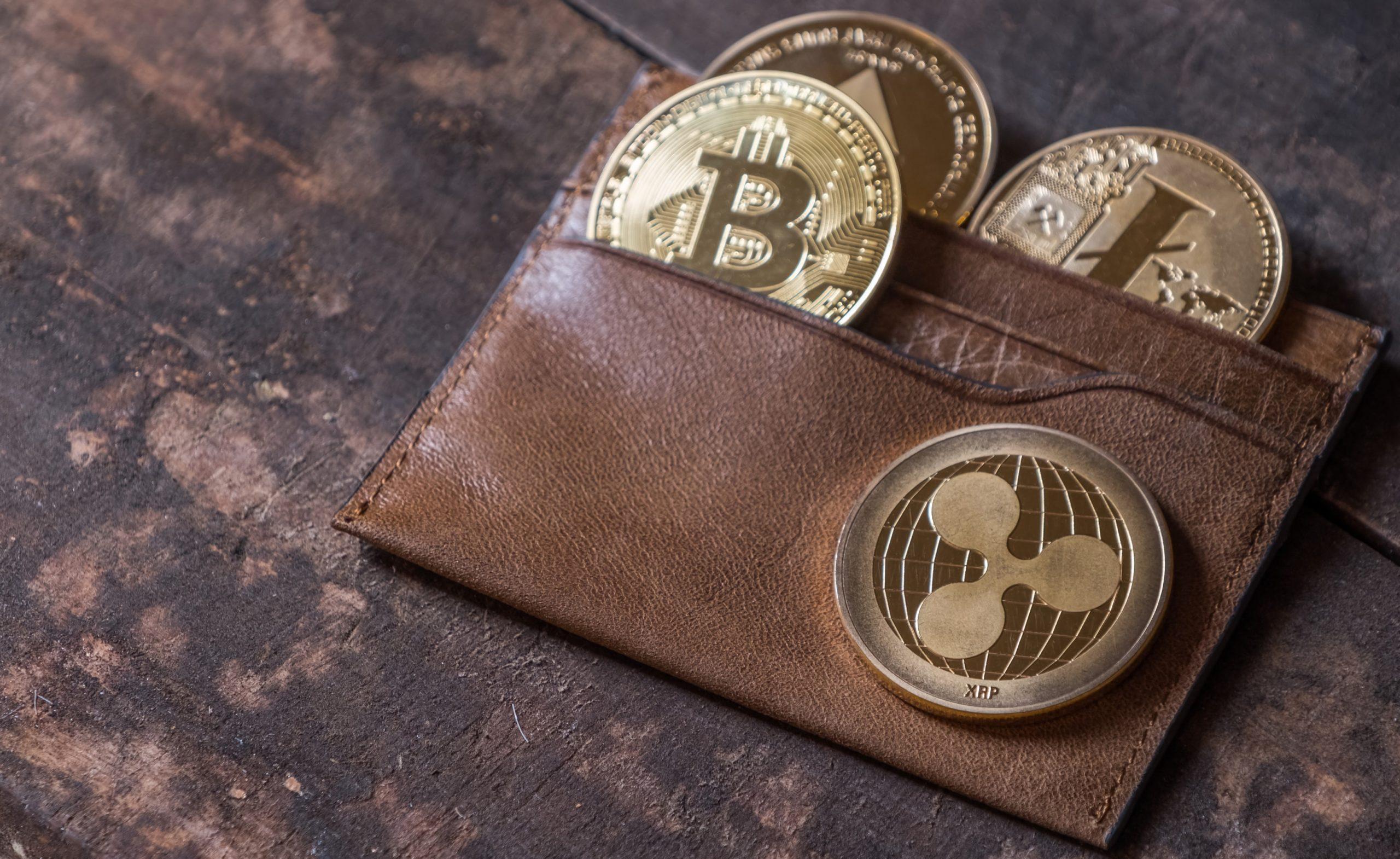 Drei Kryptomünzen in einem braunfrabigen Lederportemonaie, das auf einem hölzernen Untergrund liegt.