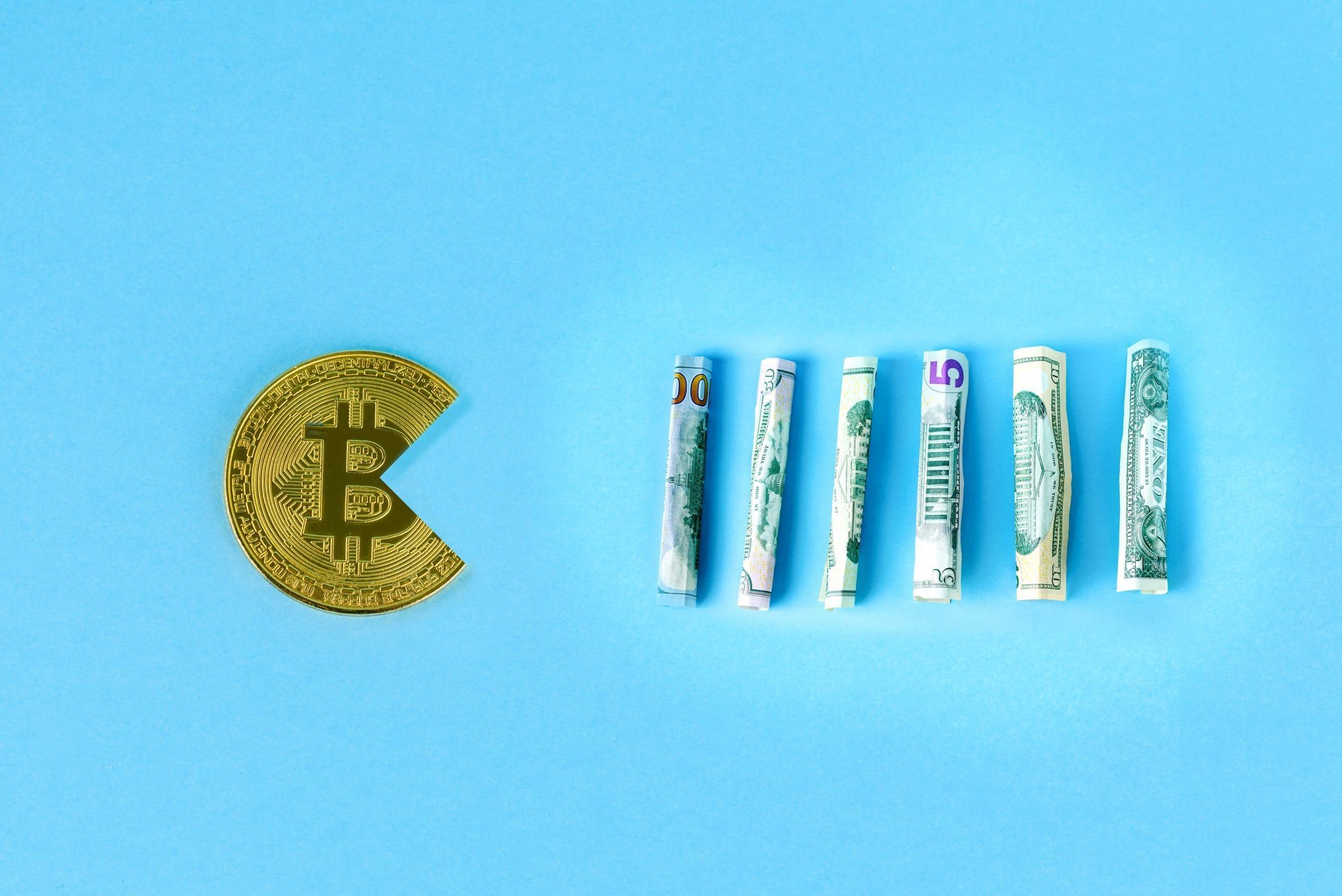 Bitcoin-Münze in Pacman-Form frisst zusammengerollte Dollar-Noten