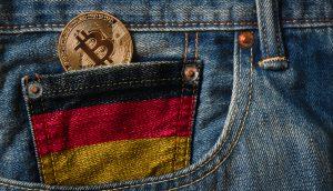 Bitcoin Münze in der schwarz-rot-goldenen Uhrentasche einer Jeans,