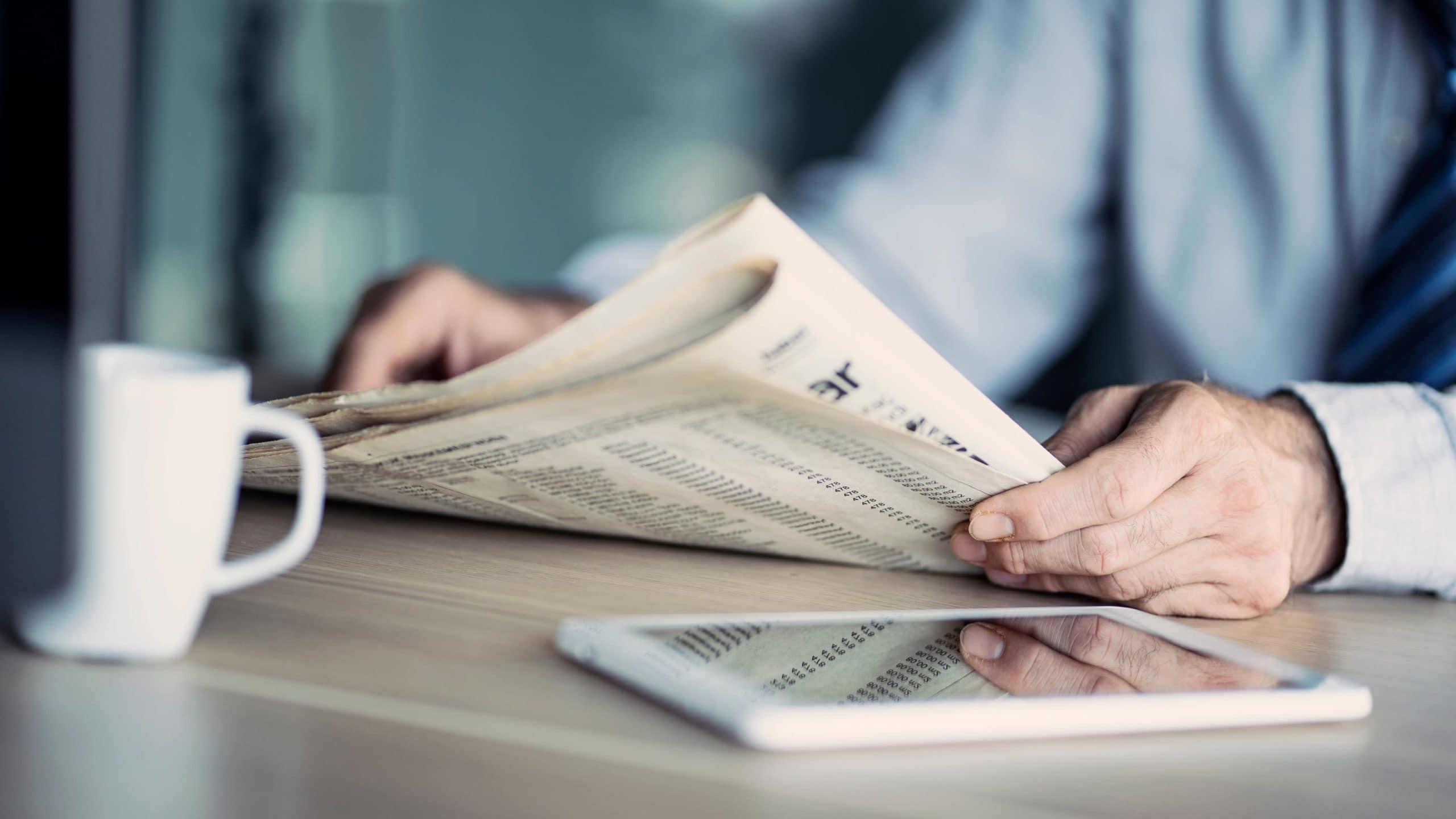 Geschägtsmann sitzt vor einem hölzernen Tisch, auf dem eine weiße Tasse steht und ein Tablet liegt und ließt Zeitung