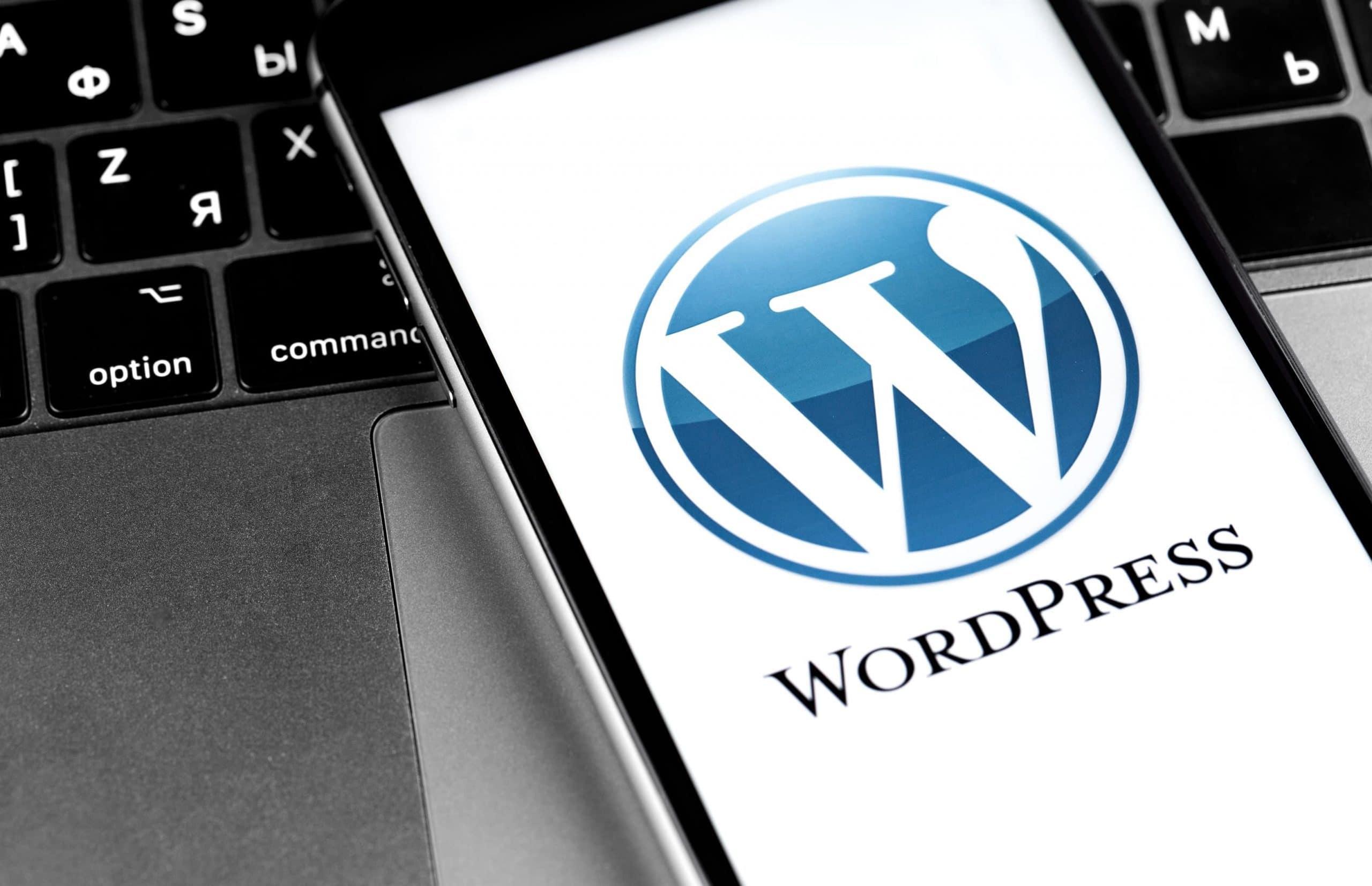 Man sieht das WordPress-Logo auf einem Smartphonebildschirm, das auf einer Laptoptastatur liegt. auf einem