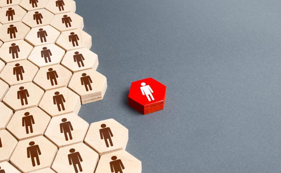 Eine rote figur, die Abseits der restilichen weißen figuren steht. Das bild ist eine Metapher für eine Kündigung.