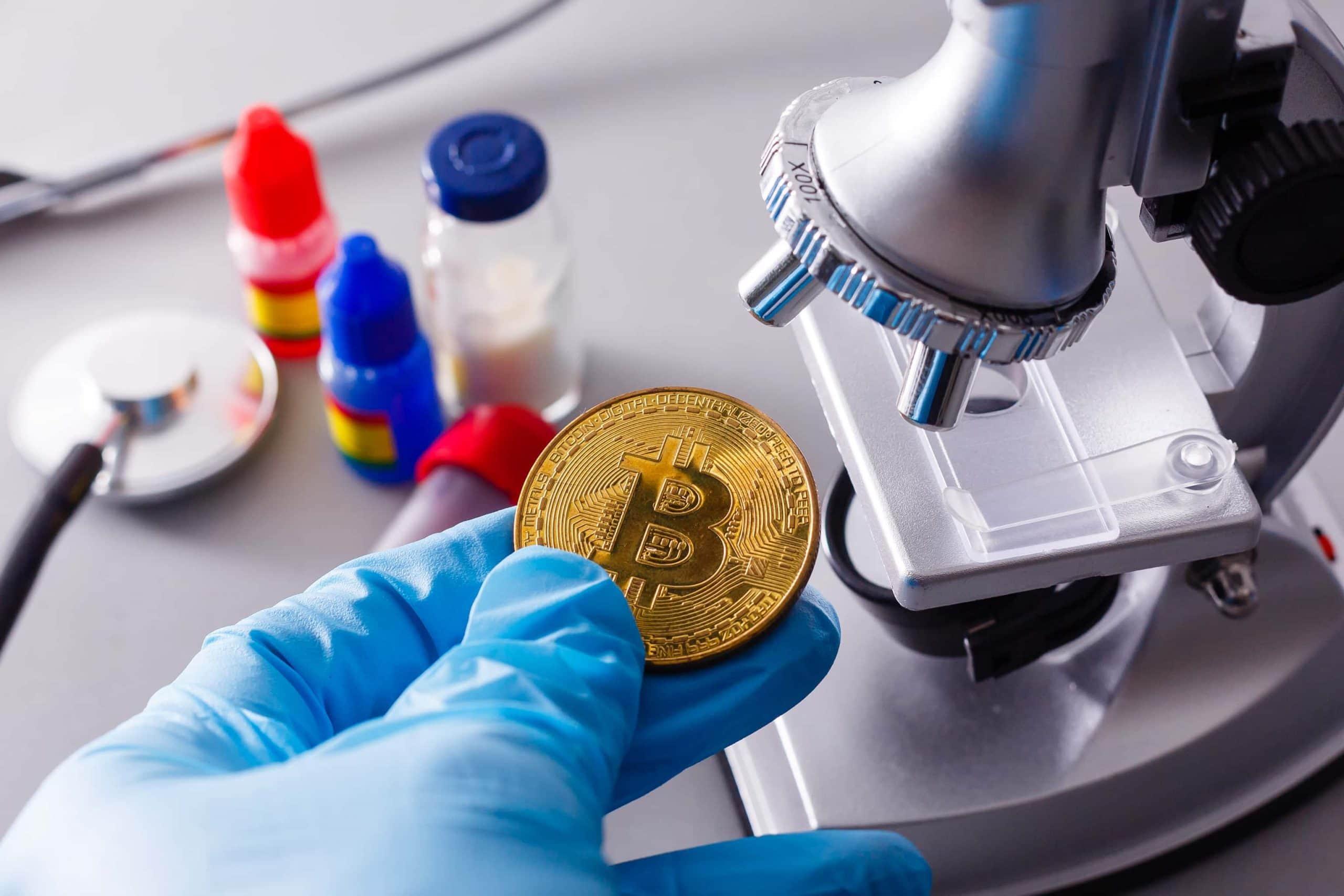 Eine Bitcoin Münze die unter ein Mikroskop gelegt wird.