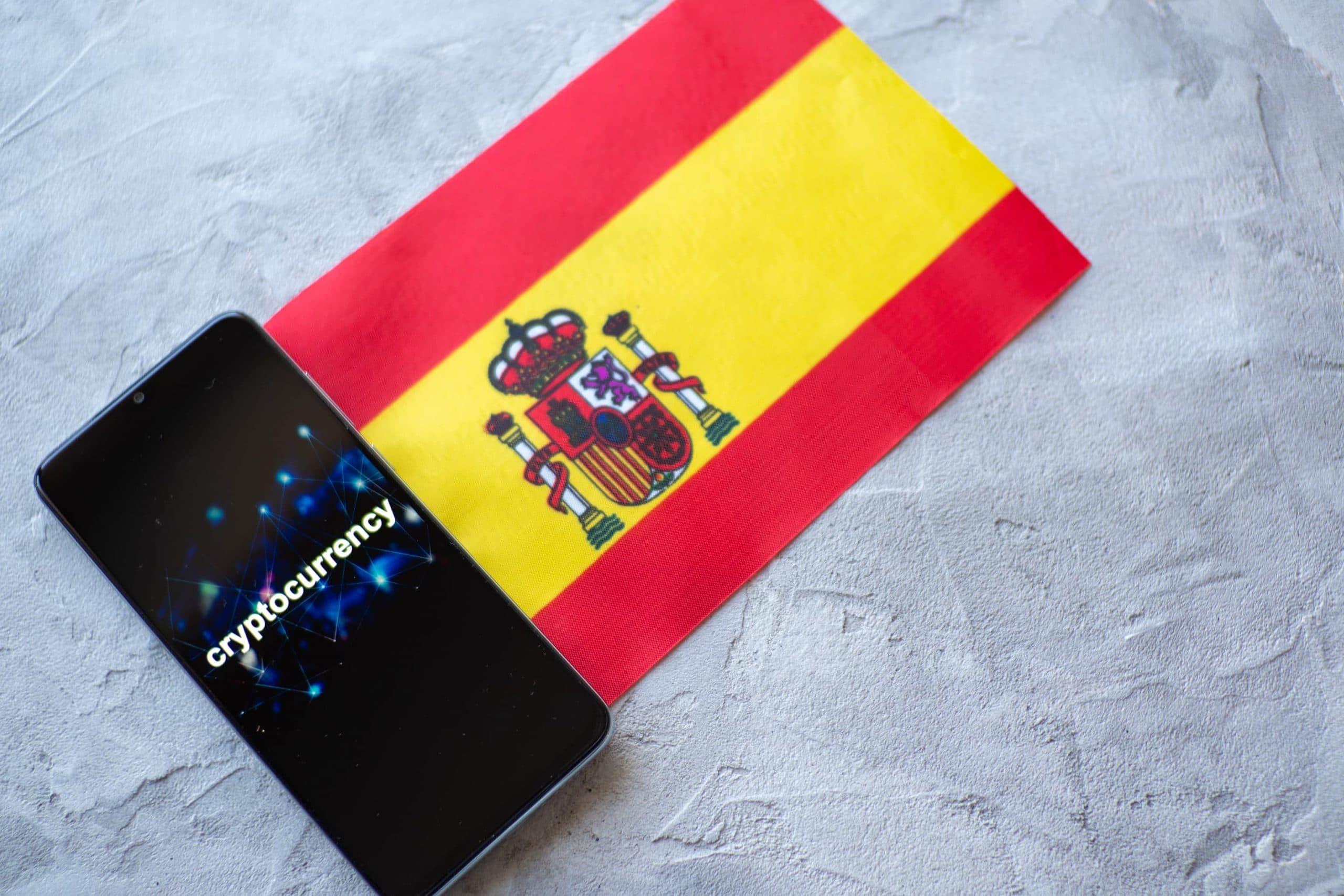 Ein Smartphone auf dem Kryptowährung auf Englisch steht, liegt neben einer ausgebreiteten spanischen Flagge, die auf einem steinernen Untergrund liegt.
