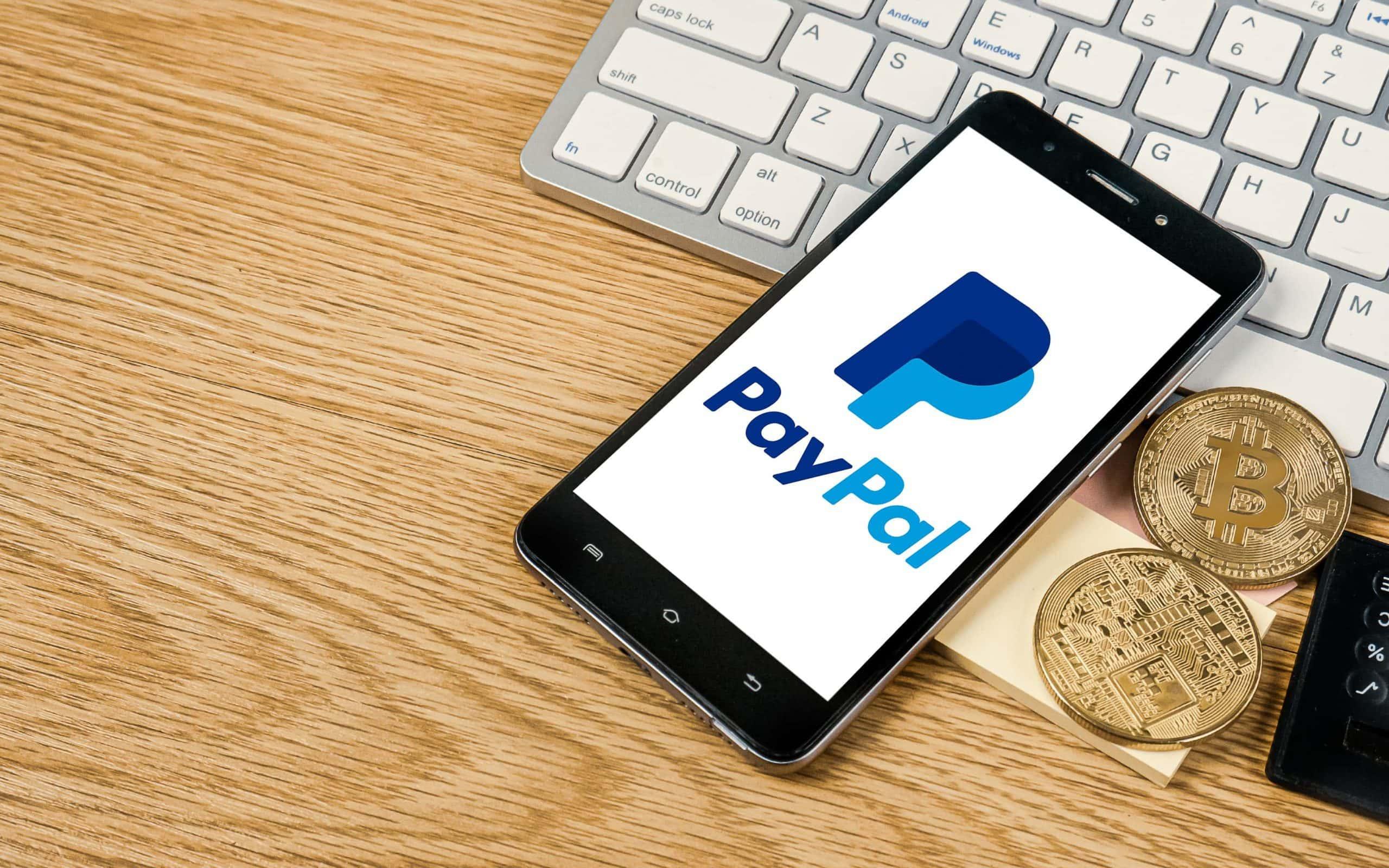 Ein Smartphone, auf dem das PayPal-Logo zu sehen ist, liegt angelehnt an eine Computertastatur auf einem Holztisch. Daneben liegen zwei Bitcoin-Münzen