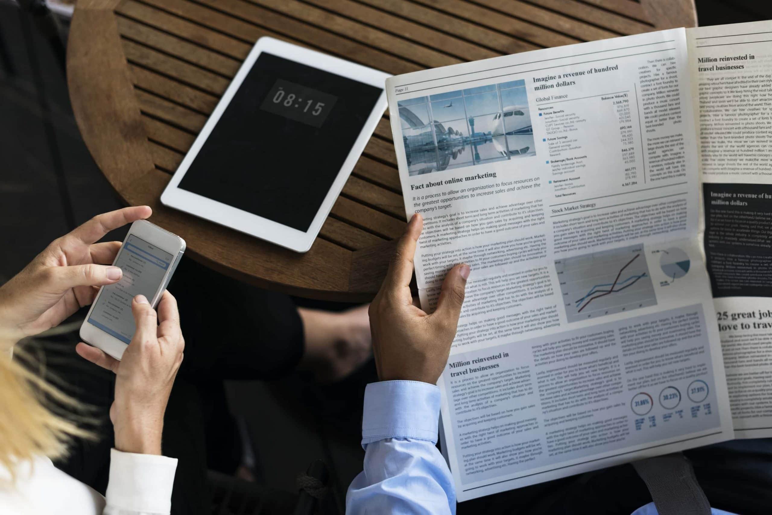 Geschäftsleute, die Nachrichten lesen. Einmal digital auf dem Smartphone und einmal klassisch in der Zeitung.