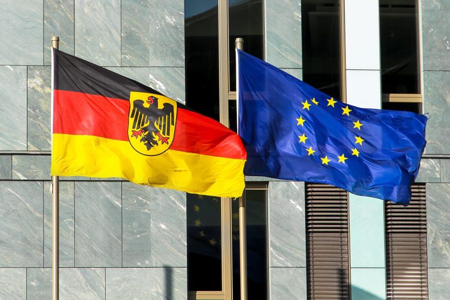 Deutsche und europäische Flagge wehen vor einem Gebäude.