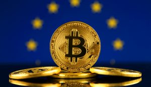 Im Vordergrund sind drei goldene Bitcoin-Münzen zu sehen. Im Hintergrund ist die Flagge der europäischen Union.