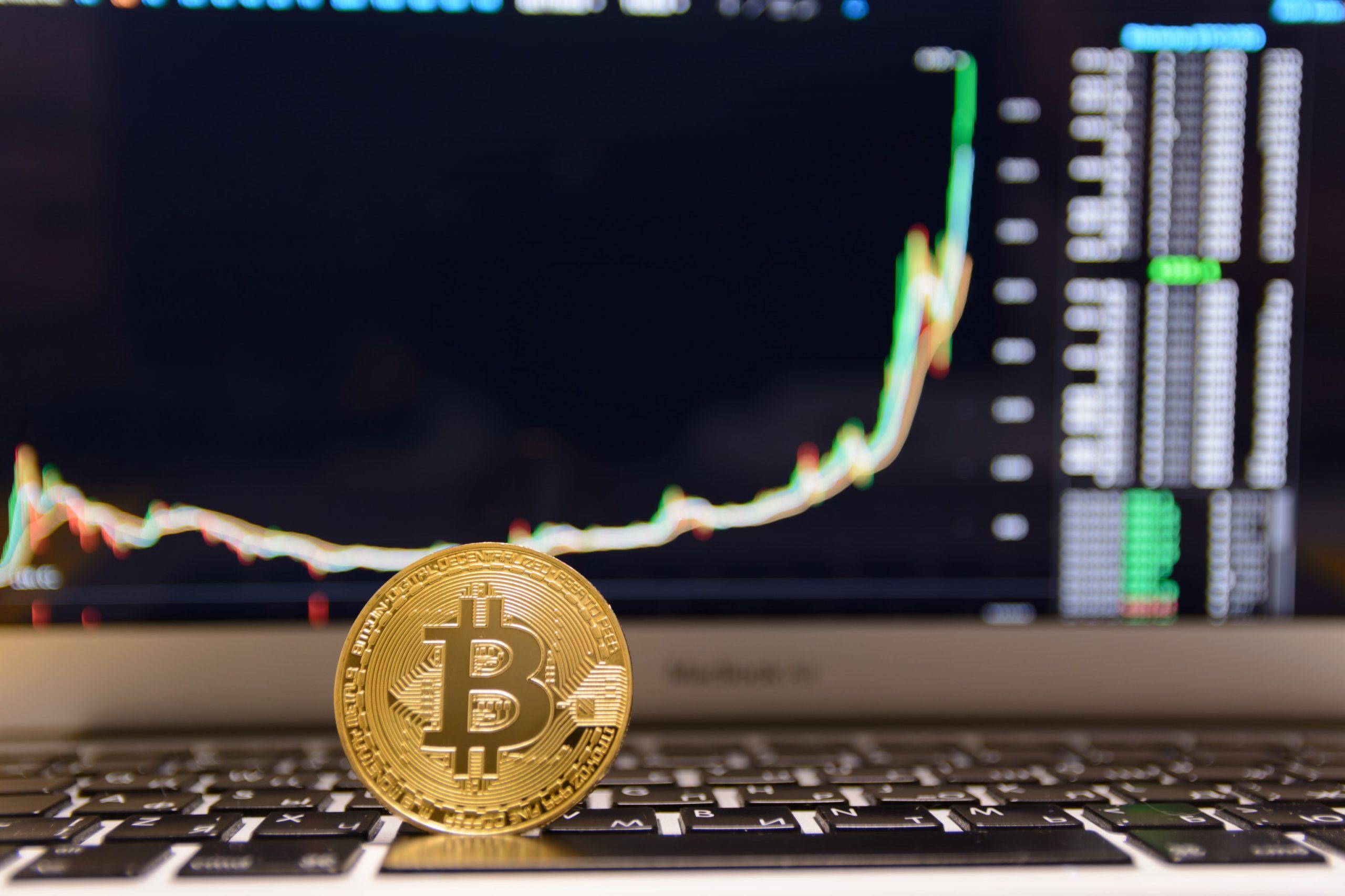 Bitcoin-Münze vor Chart mit BTC-Kurs