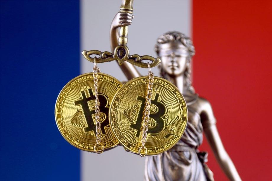 Justitia hält in ihrer Hand die Waage der Gerechtigkeit, an der zwei Bitcoin-Münzen hängen. Im Hintergrund ist die Flagge Frankreichs zu sehen.