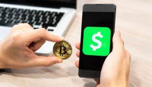 Ein Mann hält eine Bitcoin-Münue neben ein Smartphone, auf dem das Logo der CashApp zu sehen ist.