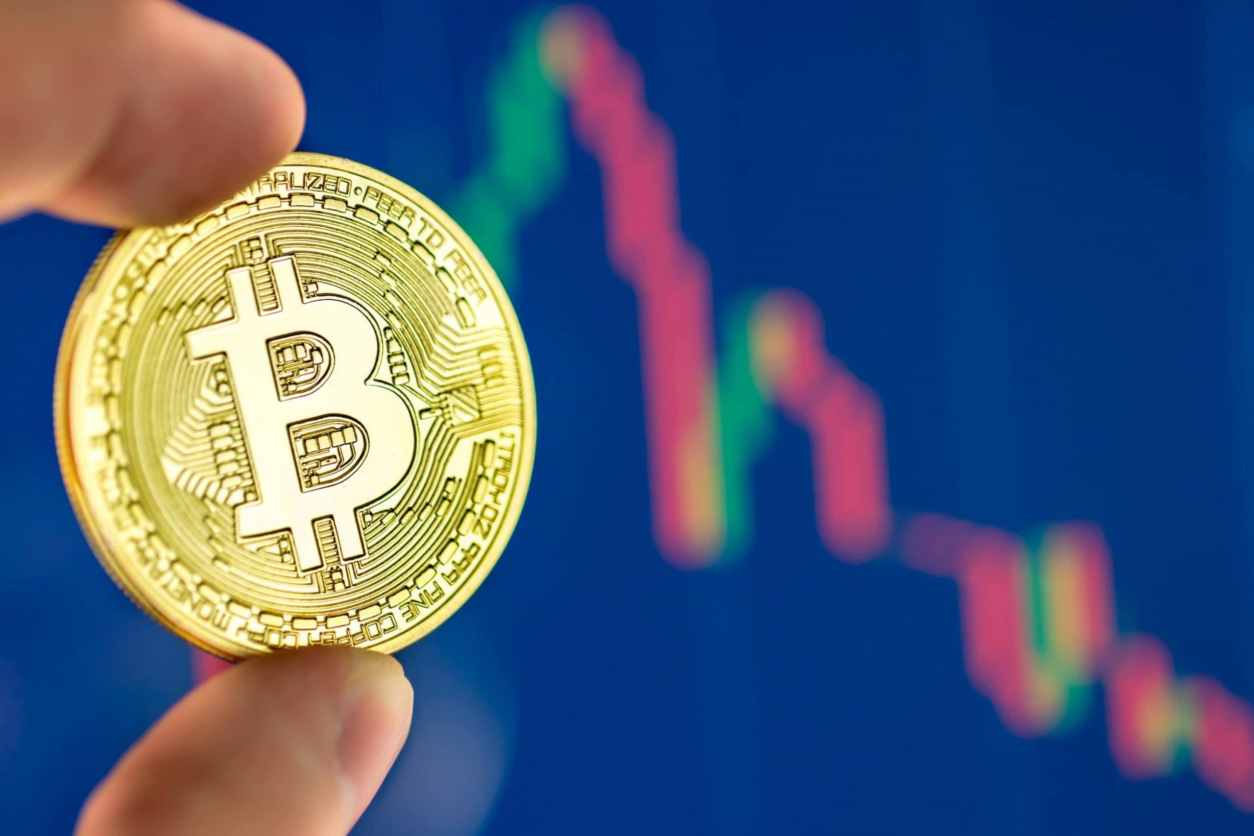 Bitcoin-Münze wird vor einem Chart gehalten