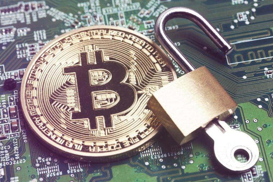 Bitcoin-Münze neben einem Schloss