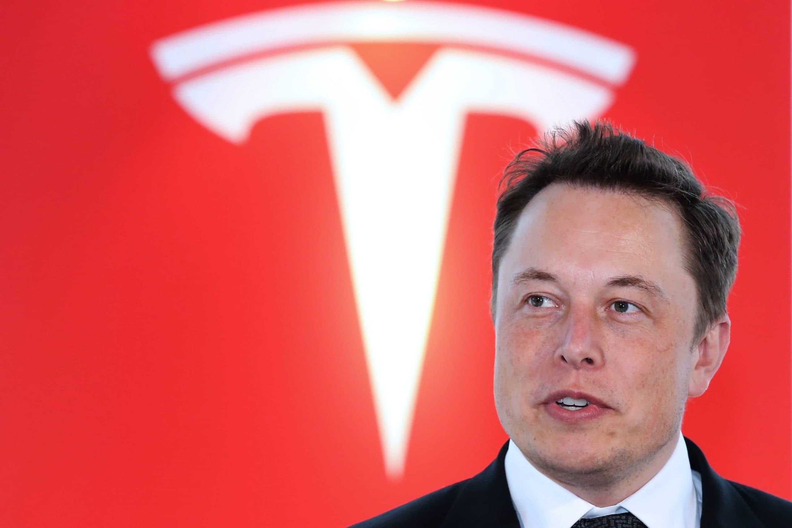 Elon Musk vor Tesla Logo