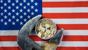 XRP-Münze in der Schraubzwinge vor US-Flagge