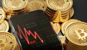 Ein roter fallender Chart auf einem Smartphone, das von Bticoin-Münzen umgeben ist
