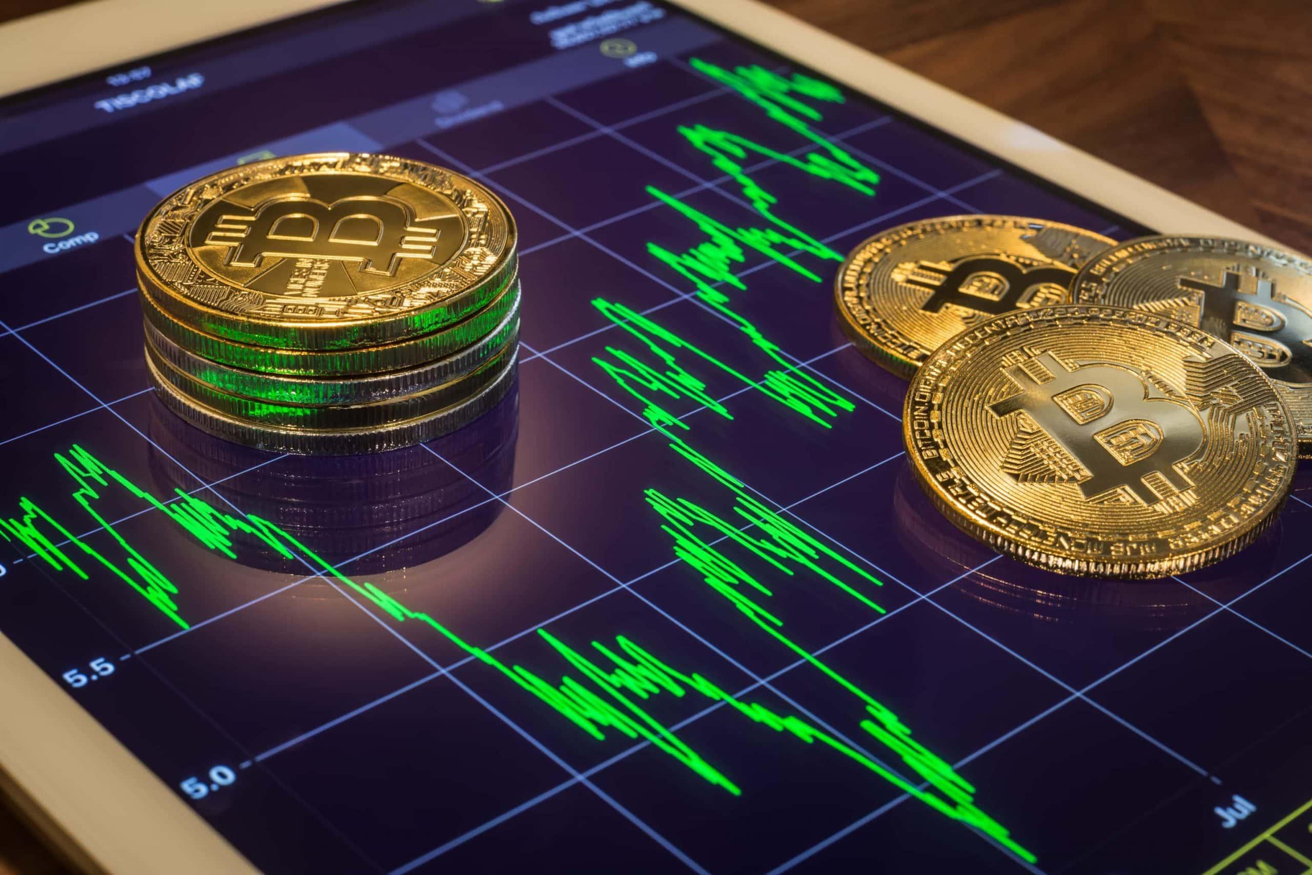 Bitcoin-Münzen auf einem Tablet, das einen Kursverlauf zeigt