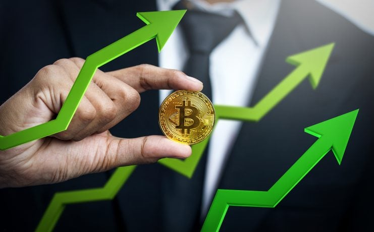 Bitcoin-Kurs: Ein Geschäftsmann hält eine Bitcoin-Münze zwischen 3 grünen Pfeilen, die nach oben zeigen