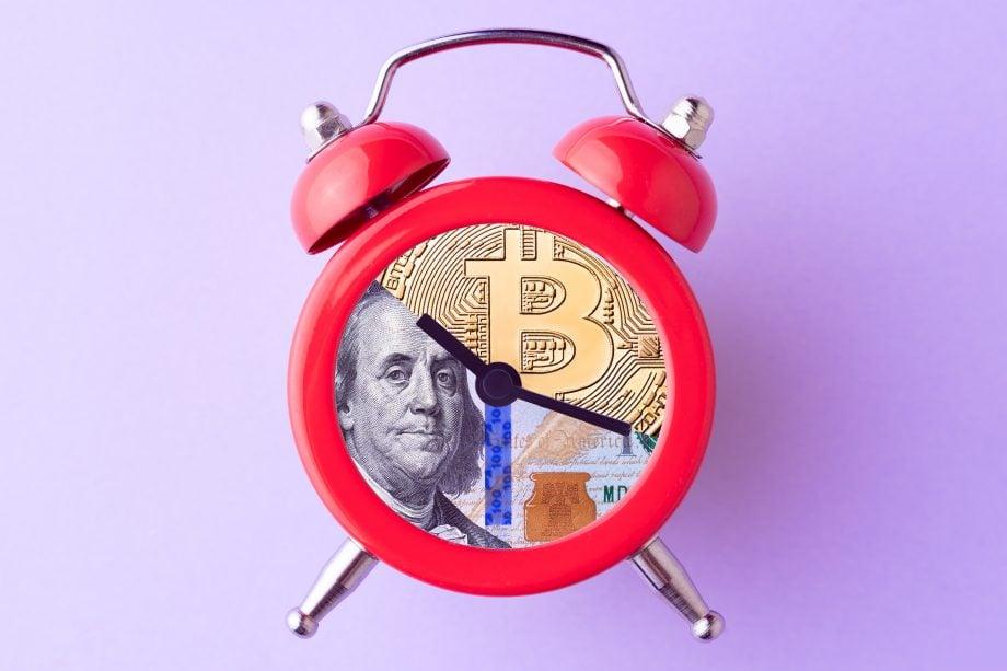 Roter Wecke, das Ziffernblatt bildet eine Collage aus Bitcoin und US-Dollar Fotos